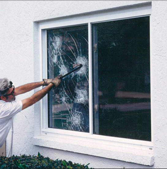 man breaking window with film
